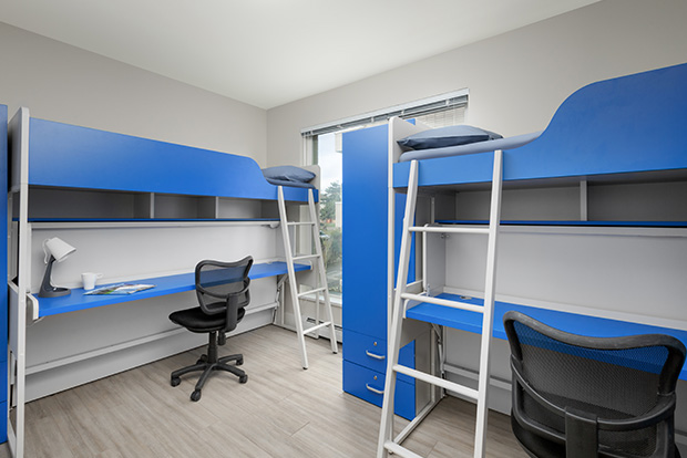 Two convertible loft beds with a bunk bed and desk for each student in a Standard Shared Bedroom at GEC Pearson student housing