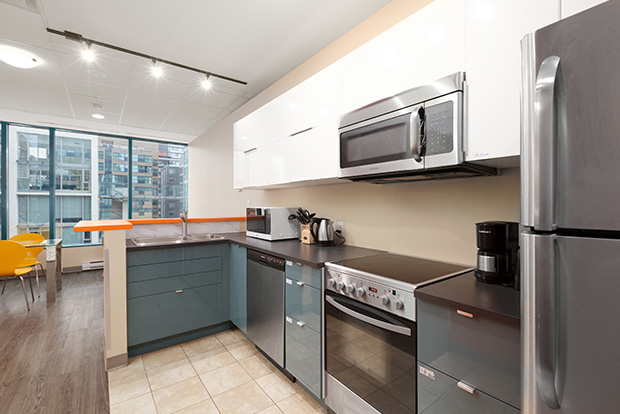 Fully equipped kitchen at GEC Viva student accommodation includes stainless steel dishwasher, refrigerator, oven, and microwave
