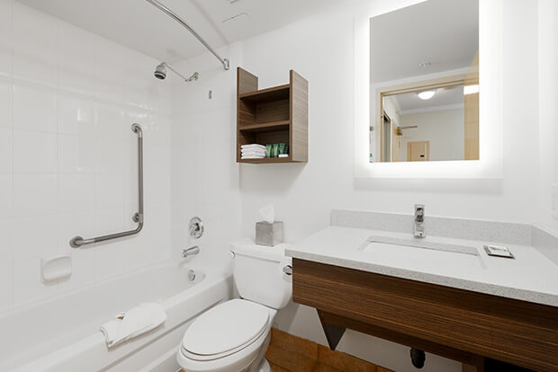 Downtown Vancouver GEC Granville Suites long term extended stays hotel has an ensuite bathroom with bathtub, standing shower, and complimentary toiletries