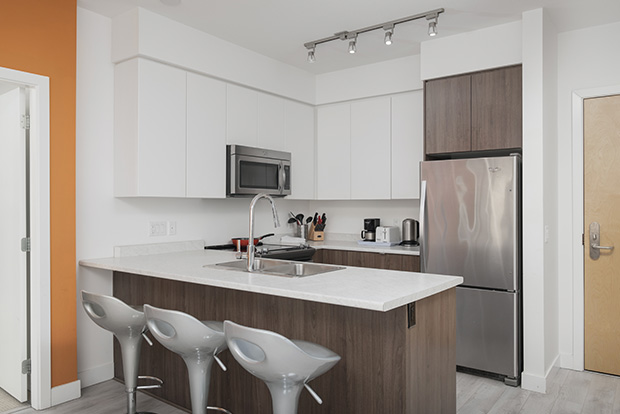 Fully equipped kitchen at GEC Burnaby Heights student housing apartment includes stainless steel dishwasher, refrigerator, oven, and microwave