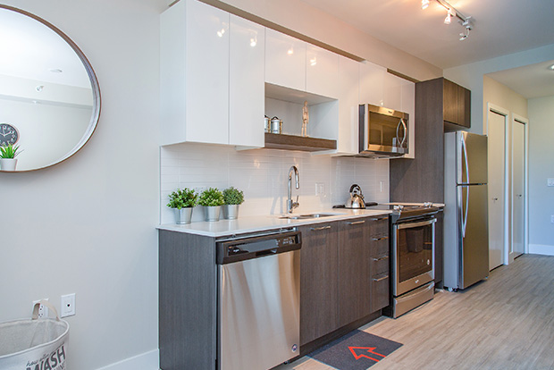 Fully equipped kitchen at GEC Pearson includes stainless steel dishwasher, refrigerator, oven, and microwave
