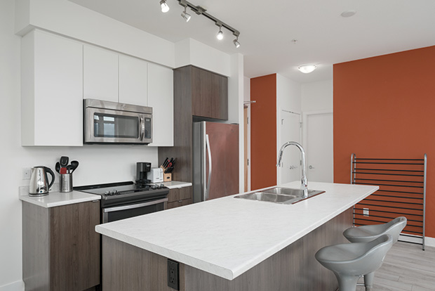 Fully equipped kitchen at GEC Burnaby Heights student residence apartment includes stainless steel dishwasher, refrigerator, oven, and microwave