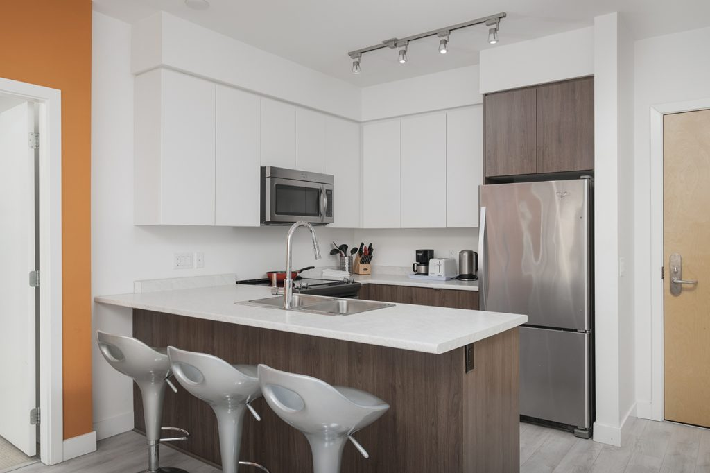 Fully equipped kitchen at GEC Burnaby Heights apartments in Vancouver include dishwasher, refrigerator, oven, microwave, utensils, cookware, kitchenware, glassware