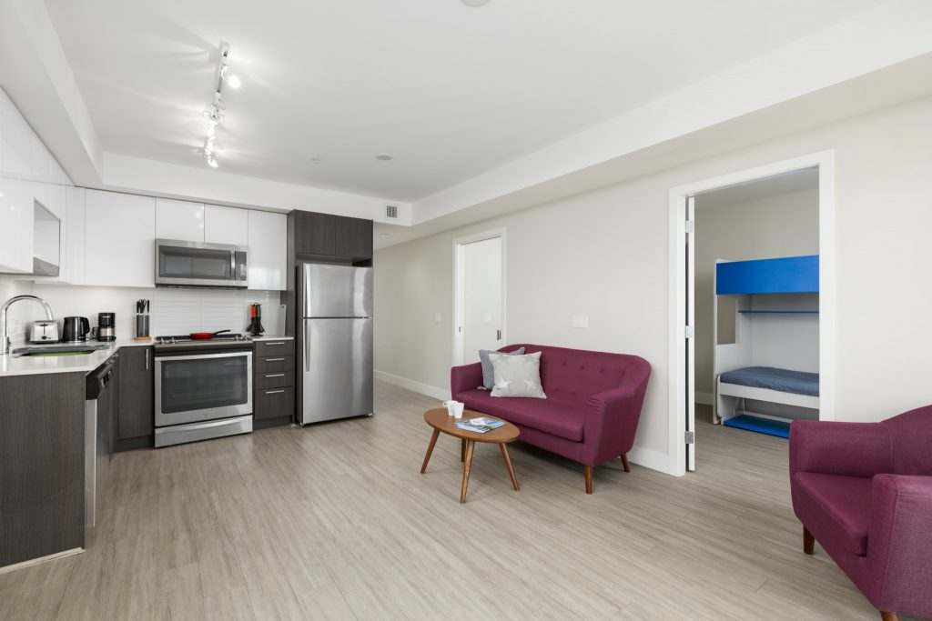 Fully furnished kitchen and living room in a GEC Pearson student housing apartment
