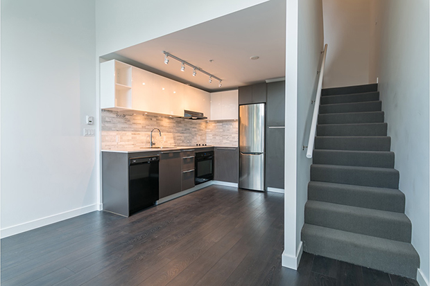Kitchen with stainless steel appliances in the GEC Marine Gateway two bedroom townhouse for rent in Vancouver