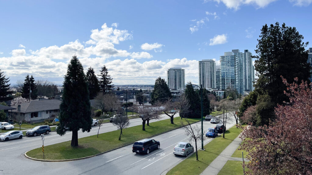 Cars on Cambie Street, partially bloomed trees, and high-rise buildings in the background.