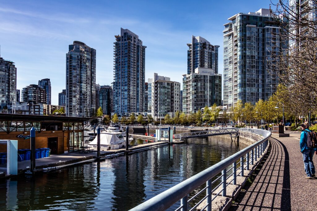 False Creek Seawall walkway. Urban style apartments along the seawall and we can see the ocean across the apartments. The cost of living in Vancouver is high because of the increased demands towards central locations.