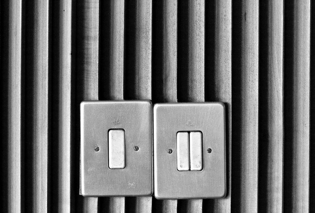 Electric switches on grey tinted walls. Save energy for environmentally friendly living.
