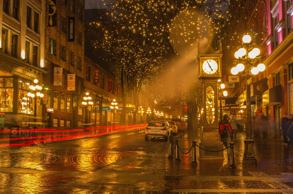 Gastown steam clock and lights shining pretty at night. One of the recommendations for Vancouver Downtown Things to Do.