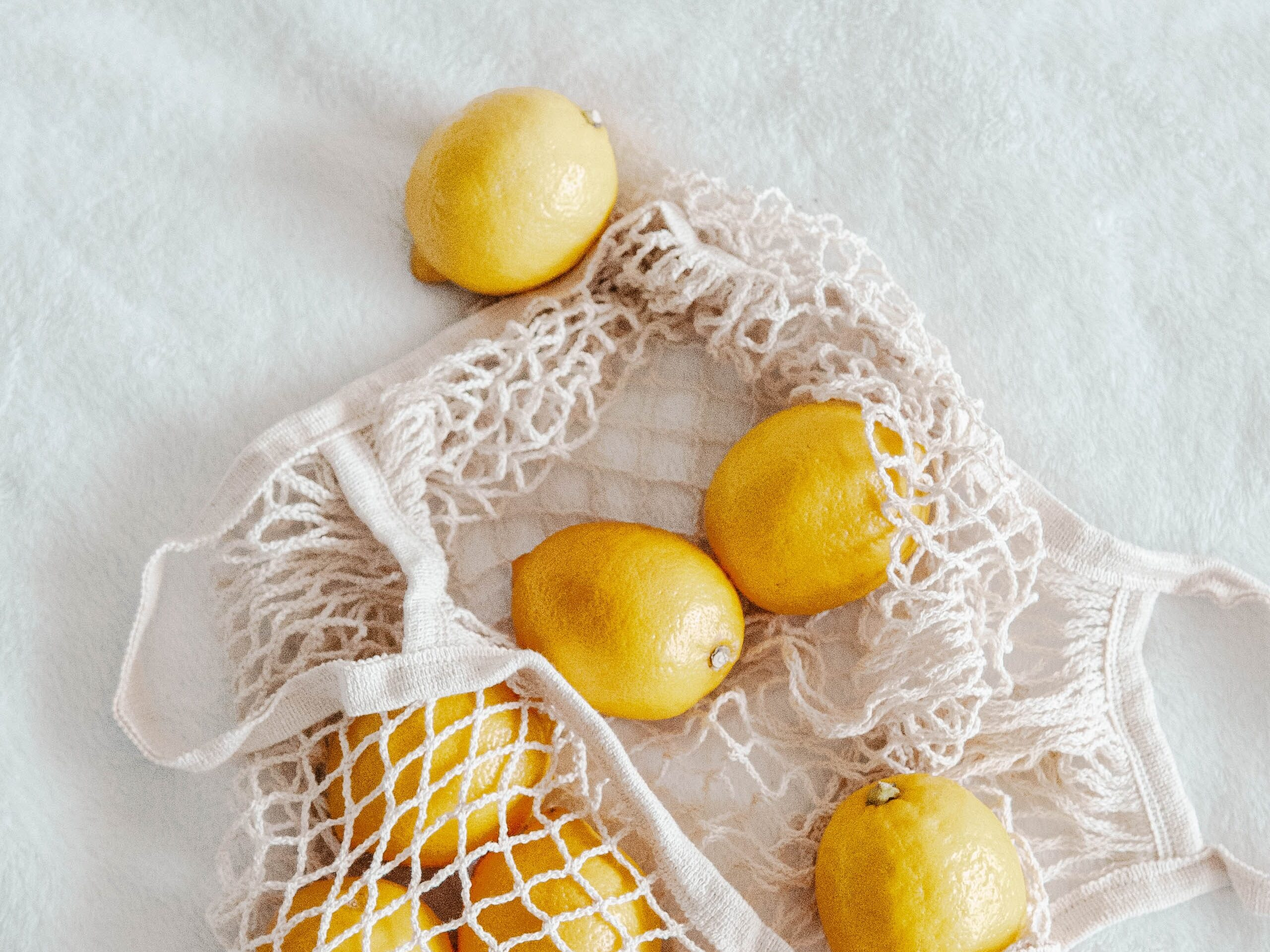 lemons spread in and out of a reusable grocery bag -- we should invest in reusable bags for environmentally friendly living.