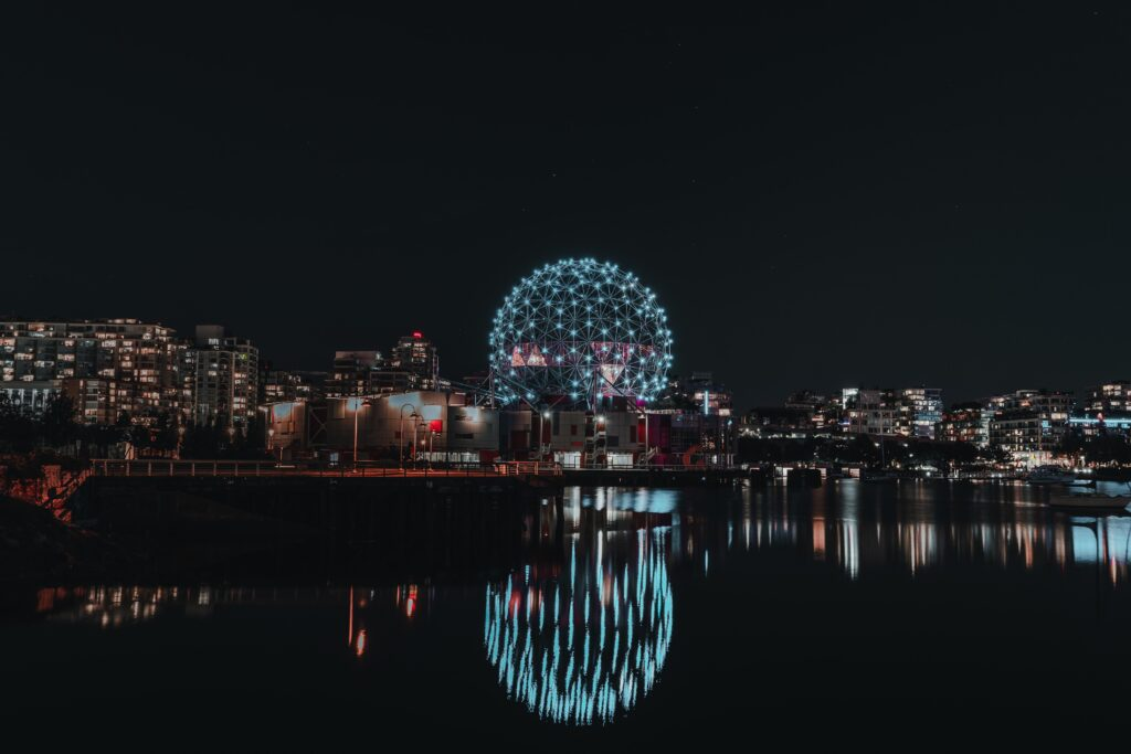 One of the recommendations for Vancouver Downtown Things to Do is walking along Olympic Village. Science World Building at night can be seen in this image.