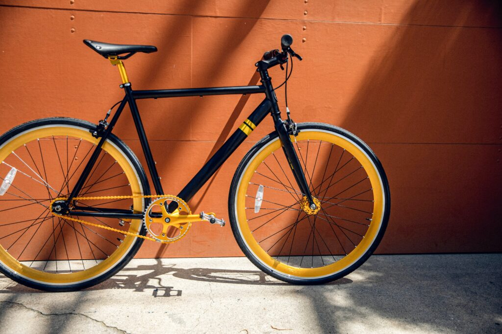 A black bike with yellow wheels standing against the wall. Biking is good for environmentally friendly living.