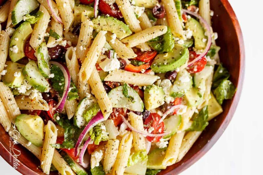 pasta salad with greens and feta cheese in a bowl