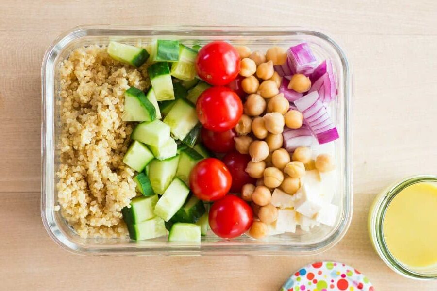 Chickpeas, quinoa, cucumbers, tomatoes, and red onion diced in a reusable glass container