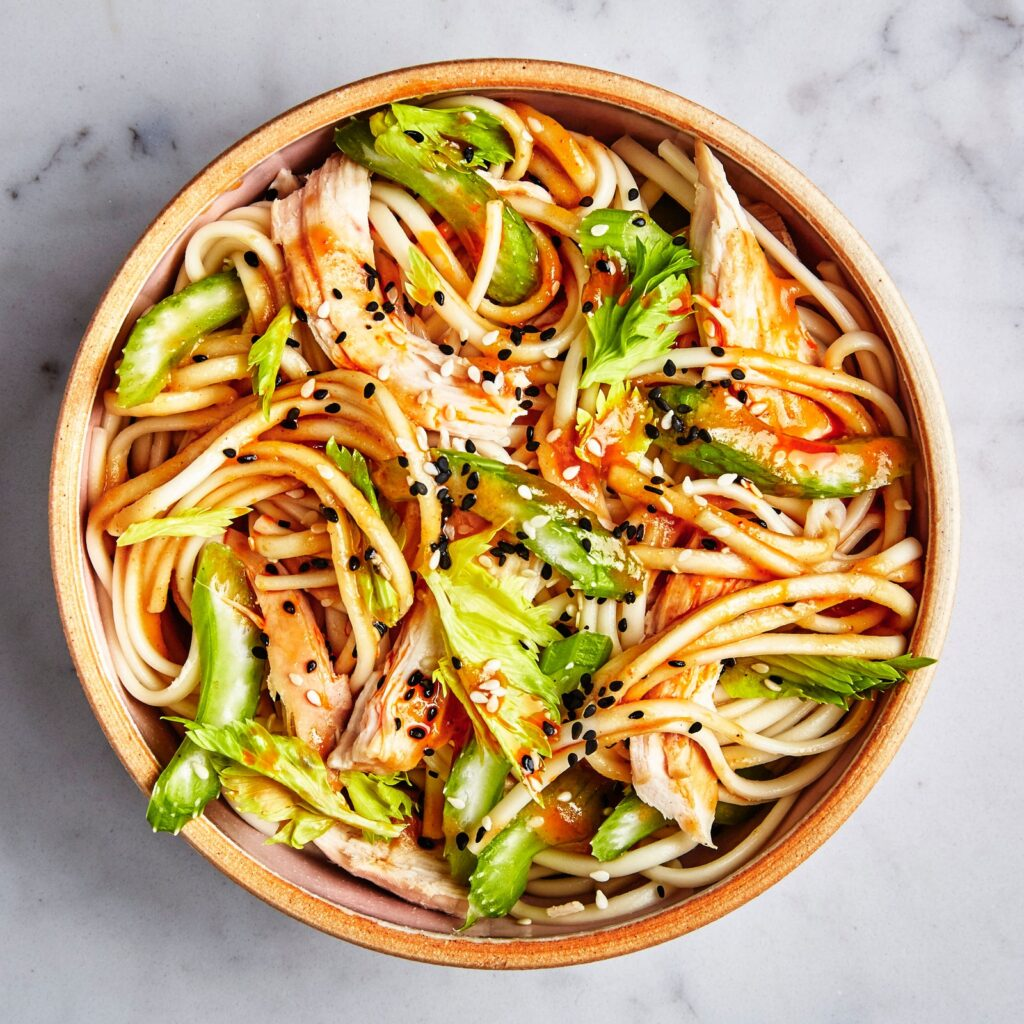 udon noodles with chicken and green beans in a bowl